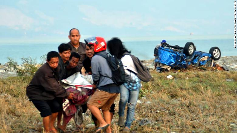 People carry a victim of the disaster in Palu on September 29.