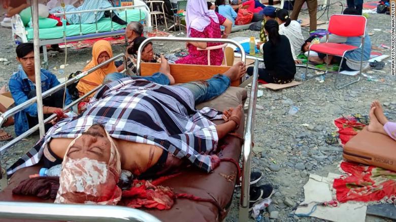 Earthquake survivors rest on beds outside a hospital in Palu on September 29.