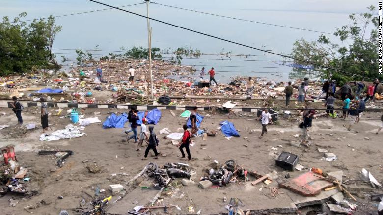 Rescuers walk among debris after a series of earthquakes and a tsunami in Palu on Friday.