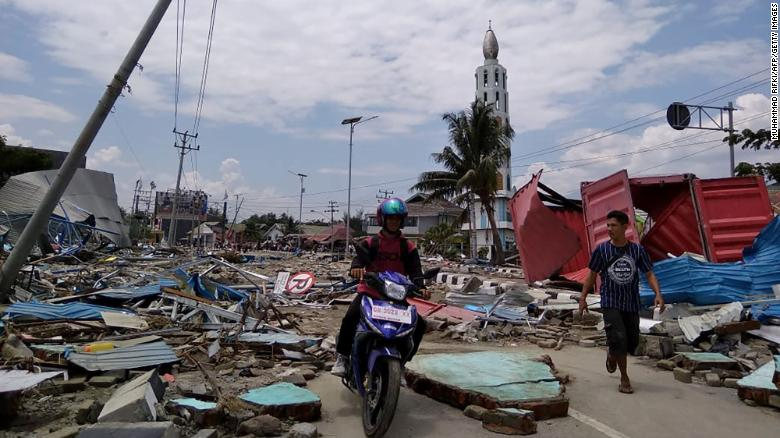 Residents make their way along a street full of debris September 29 in Palu, a coastal city of about 350,000.
