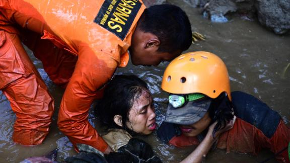 Rescuers try to free a 15-year-old earthquake survivor who was trapped in the flooded ruins of a collapsed house in Palu on Sunday, September 30.