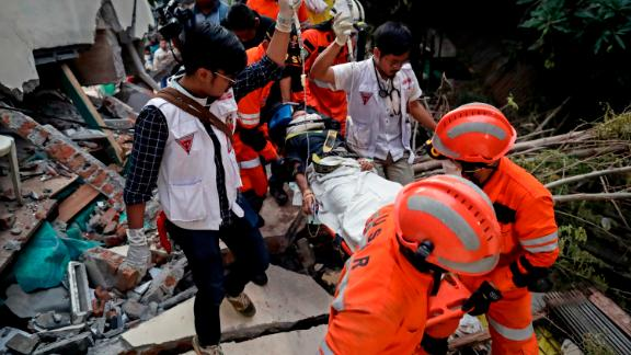 Rescuers move a survivor from a collapsed restaurant building in Palu.