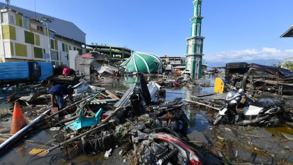 A resident sifts through debris past the rubble of a mosque in Palu, Indonesia