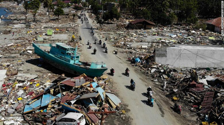 People on motorbikes pass a boat and other debris in Palu, Indonesia, on Monday, October 1, after an earthquake and tsunami hit the area on September 28.