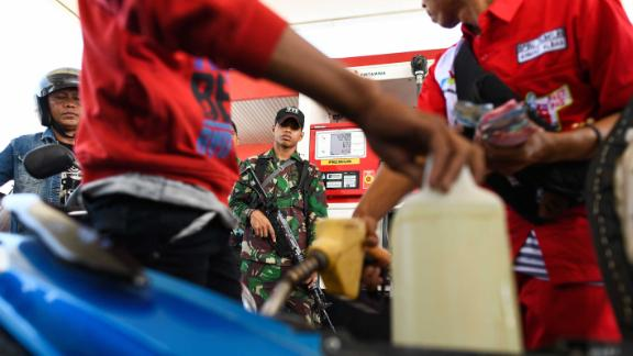 An Indonesian soldier stands guard at a service station as people line up to fill gasoline containers on October 1.