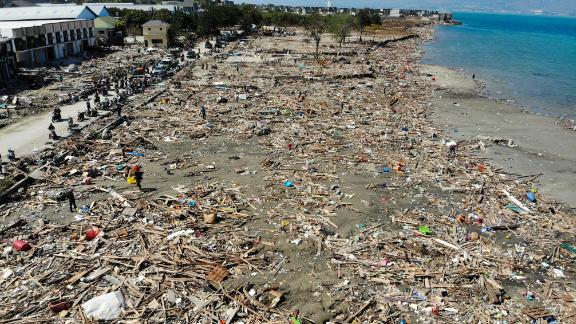 TOPSHOT - Earthquake survivors search for useable items among the debris in Palu, Indonesia