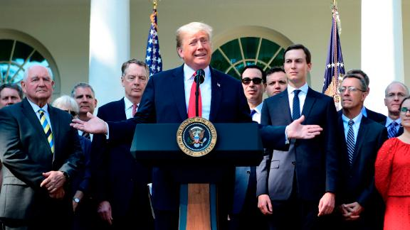 US President Donald Trump surrounded by staff speaks from the Rose Garden of the White House in Washington, DC, remarking on the United StatesMexicoCanada Agreement on October 1, 2018. (Photo by Jim WATSON / AFP)        (Photo credit should read JIM WATSON/AFP/Getty Images)