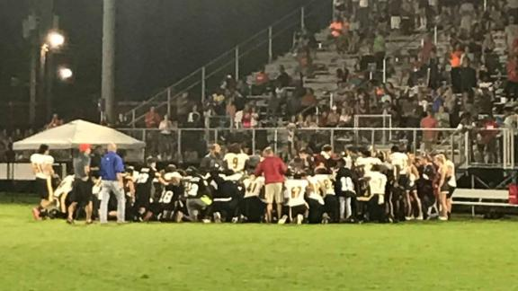 Football players and coaches from Pike County and Peach County high schools knelt in prayer after Dylan Thomas was taken to the hospital on September 28, 2018.