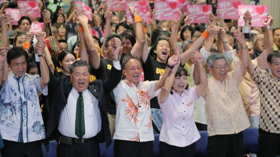 Danny Tamaki (C), the son of a US Marine and Japanese mother, celebrates after he was elected on September 30.