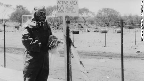 A man in protective clothing at Maralinga with a camera also protected by a plastic cover.