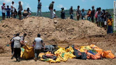 Officials carry body bags into a mass grave ahead of a funeral for quake victims in Palu on Monday.