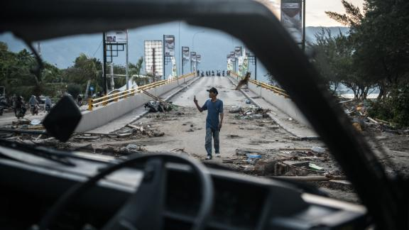 A man takes a photo on a damaged bridge in Palu on October 1.