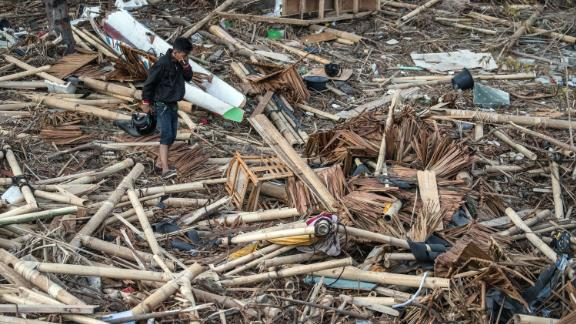 PALU, INDONESIA - OCTOBER 01: A man covers his nose as he walks through the rubble and debris of a building that was destroyed by a tsunami, on October 01, 2018 in Palu, Indonesia. Over 844 people have been confirmed dead after a tsunami triggered by a magnitude 7.5 earthquake slammed into Indonesia