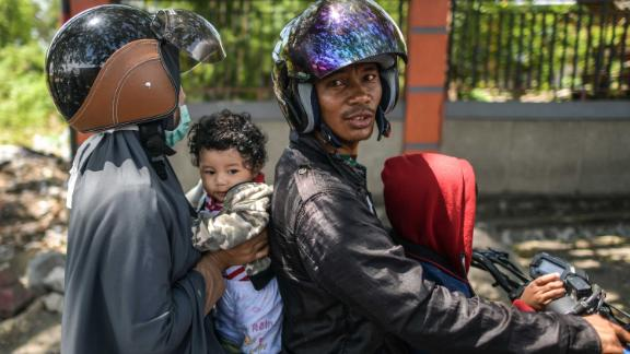 A family on a motorcycle waits to learn the status of relatives on October 2.