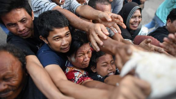 Survivors scuffle for live chickens being distributed from a police truck in Palu on October 2.