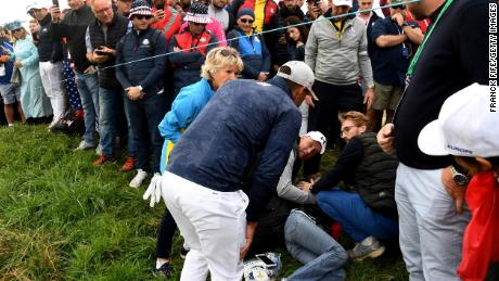 US golfer Brooks Koepka attends injured spectator Corine Remande at the Ryder Cup near Paris.
