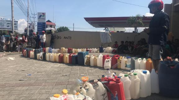 Bottles line up outside a petrol station in the city of Palu, waiting to be filled with precious fuel.