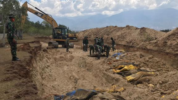 Almost 200 bodies have been buried in a mass grave on the outskirts of Palu.