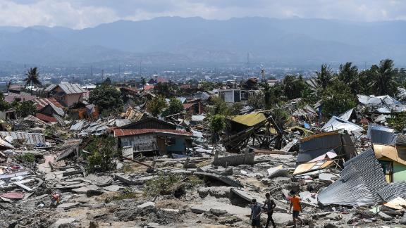 Residents walk amid debris in Palu on Tuesday.