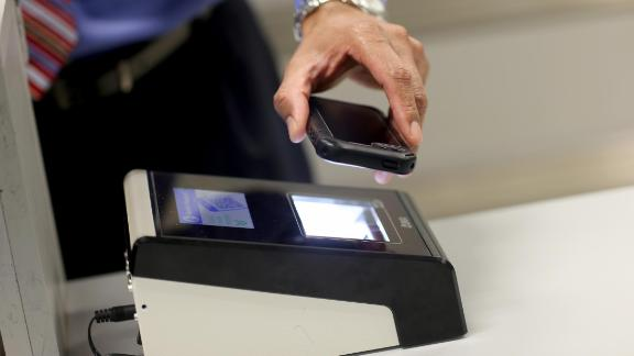 A passenger scans a phone boarding pass. Travelers arriving in New Zealand could now face fines if they refuse to allow their devices to be searched by border officials.