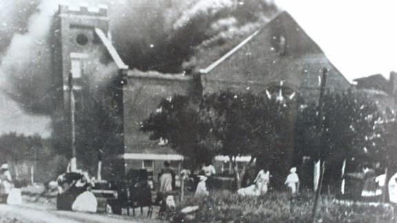 Smoke rolls out of Mount Zion Baptist Church after white mobs torched the building.