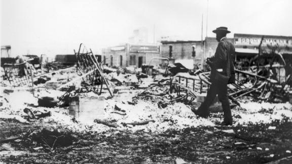 A man photographs iron beds amid the ashes of a burned-out block after the Tulsa massacre.