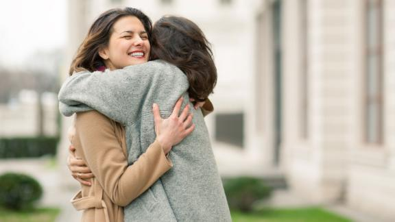 Two girls hug on the sidewalk. Feel joyfull and happy togather.; Shutterstock ID 460254745; Project Name: -