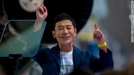 Japanese billionaire Yusaku Maezawa reacts during the announcement by Elon Musk to be the first private passenger who will fly around the Moon aboard the SpaceX BFR launch vehicle, at the SpaceX headquarters and rocket factory on September 17, 2018 in Hawthorne, California. - Japanese billionaire businessman, online fashion tycoon and art collector Yusaku Maezawa was revealed as the first tourist who will fly on a SpaceX rocket around the Moon. (Photo by DAVID MCNEW / AFP) (Photo credit should read DAVID MCNEW/AFP/Getty Images)