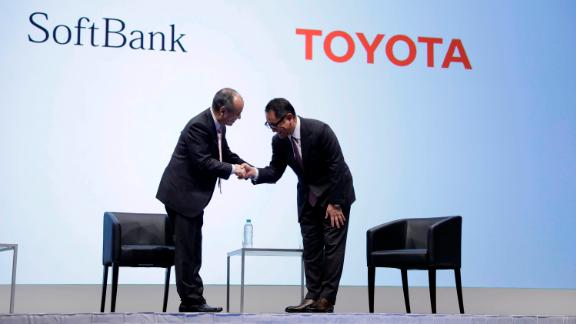 Masayoshi Son, chairman and chief executive officer of SoftBank Group Corp., left, shakes hands with Akio Toyoda, president of Toyota Motor Corp., during a news conference in Tokyo, Japan, on Thursday, Oct. 4, 2018. Japan's SoftBank and Toyota are teaming up on ride-hailing and self-driving cars as they accelerate their push into a market dominated by U.S. technology and car companies. Photographer: Kiyoshi Ota/Bloomberg via Getty Images