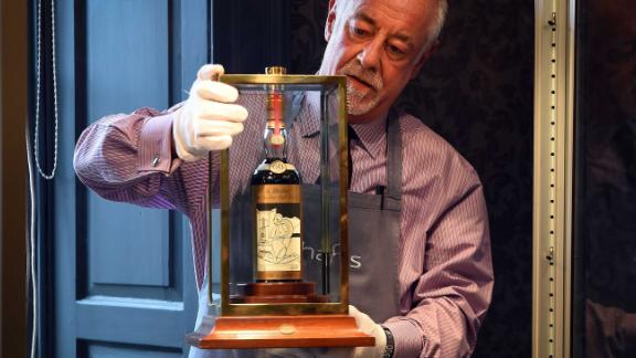 A Bonhams porter shows the bottle of Macallan Valerio Adamai 1926 whisky which sold for a world record sale price of £700,000 at auction in Edinburgh on October 3, 2018. - The whisky, which was in a vat for 60 years from 1926 then bottled, fetched £700,000 plus a £148,000 sales premium to make it the most expensive whisky for £848,000. (Photo by Andy Buchanan / AFP)        (Photo credit should read ANDY BUCHANAN/AFP/Getty Images)