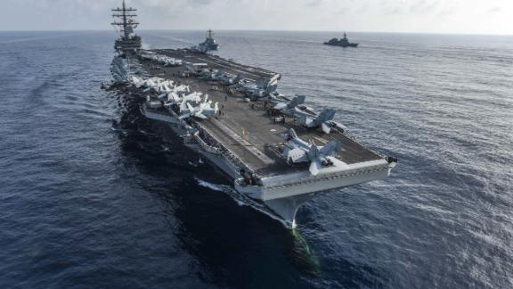 SOUTH CHINA SEA (Aug. 31, 2018) The aircraft carrier USS Ronald Reagan (CVN 76) and the guided-missile destroyer USS Milius (DDG 69), center, conduct a photo exercise with Japan Maritime Self-Defense Force ships.  (US Navy photo by Mass Communication Specialist 2nd Class Kaila V. Peters/Released)