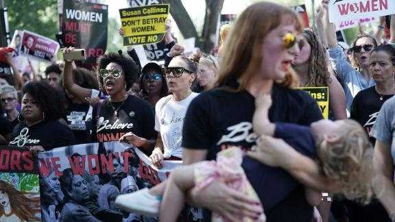 WASHINGTON, DC - OCTOBER 04:  Demonstrators shout slogans as they march towards U.S. Supreme Court for a rally October 4, 2018 in Washington, DC. Activists are holding a rally to protest against Supreme Court associate justice nominee Brett Kavanaugh.  (Photo by Alex Wong/Getty Images)