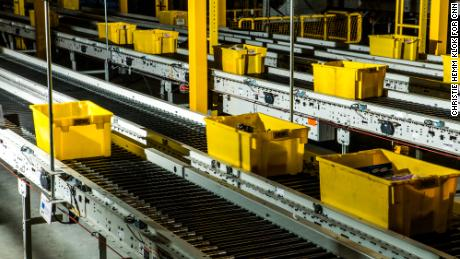Crates zip through the fulfillment center on a conveyor belt.