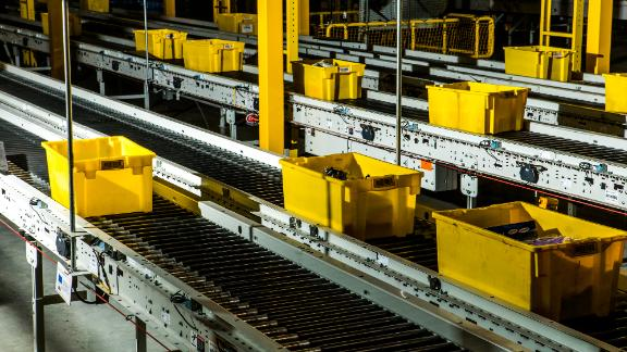 Yellow crates zip through the warehouse on a conveyor belt.