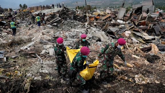 Soldiers carry a dead body from the ruins of houses in Palu, Indonesia, on Thursday, October 4.