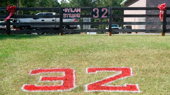 """Red ribbons, the number 32 and """"#DylanStrong"""" are seen in front of a small business Friday in Zebulon, Georgia, the home of Pike County High School."""