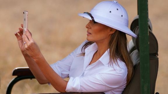 First lady Melania Trump takes photos with her cell phone during a safari at Nairobi National Park in Nairobi, Kenya, Friday, Oct. 5, 2018. Melania Trump has fed baby elephants as she visits a national park in Kenya to highlight conservation efforts. The U.S. first lady also went on a quick safari. Mrs. Trump is on her first-ever visit to Africa and her first extended solo international trip as first lady.  (AP Photo/Carolyn Kaster)
