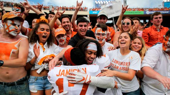 Texas Longhorns defensive back D'Shawn Jamison and defensive back P.J. Locke III celebrate with fans after their game against the Oklahoma Sooners at the Cotton Bowl on October 6, 2018. The Lornghorns won the Red River Showdown by a score of 48-45.