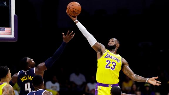 Los Angeles Lakers forward LeBron James grabs a rebound over Denver Nuggets forward Paul Millsap during the first half of an NBA preseason basketball game on Sunday, September 30, 2018.