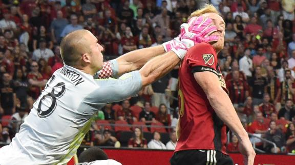 New England Revolution goalkeeper Brad Knighton grasps the face of Atlanta United defender Jeff Larentowicz during the first half of their match on October 6, 2018 at Mercedes-Benz Stadium in Atlanta, Georgia.