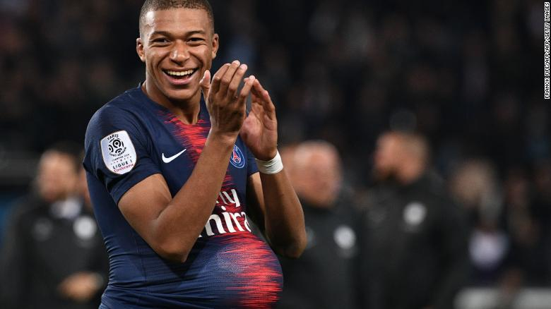 Mbappe hides the match's ball under his jersey after scoring four goals against Lyon.