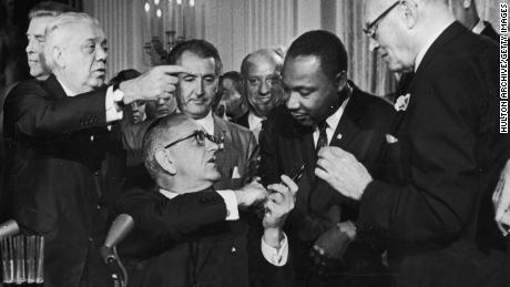 While holding multiple pens, President Lyndon Johnson greets the Rev. Martin Luther King Jr. at the signing of the 1964 Civil Rights Act.