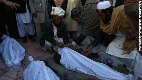 Afghans mourn after four children were killed in an airstrike in Ghazni Province on February 7.