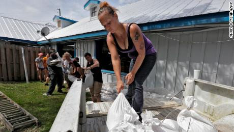 Krystal Day, of Homosassa, Fla., leads a sandbag assembly line at the Old Port Cove restaurant on Tuesday in Ozello, Fla.