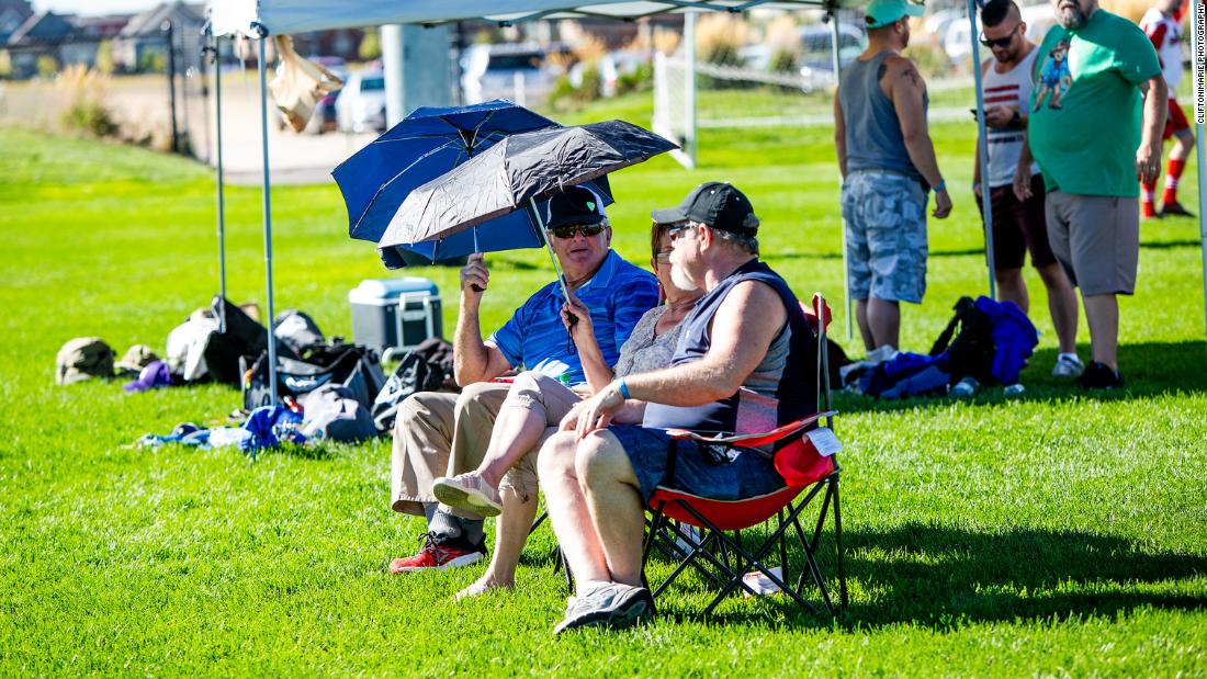 Fans shade themselves with umbrellas to guard against the 100 degrees Fahrenheit heat in Denver.
