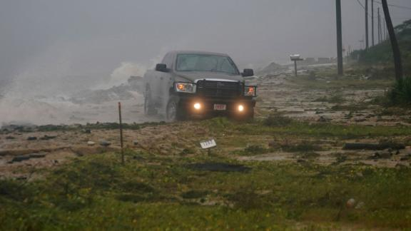 A truck drives along a road in Alligator Point, Florida, that had been washed out by the storm on October 10.