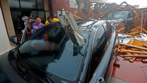 A woman checks on her vehicle after a hotel canopy collapsed in Panama City Beach.