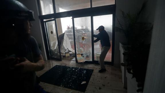 A hotel employee holds a glass door closed as it breaks from flying debris during Hurricane Michael in Panama City Beach, Fla., Wednesday, Oct. 10, 2018. (AP Photo/Gerald Herbert)