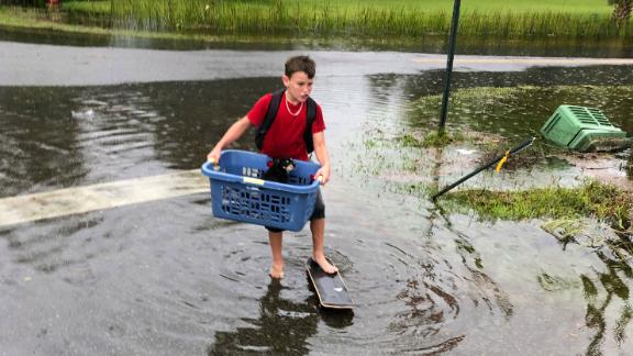 Jayden Morgan, 11, evacuates his home as water starts to flood his neighborhood in St. Marks.