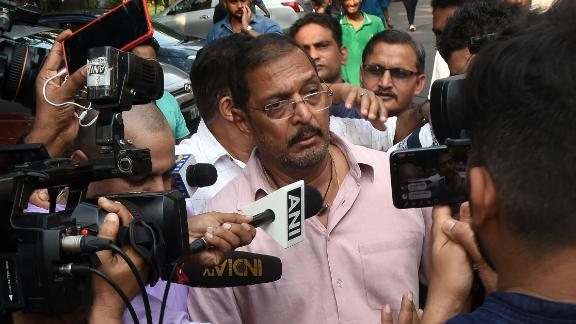 Indian Bollywood actor Nana Patekar is mobbed by the media as he leaves after making a statement outside his home in Mumbai on October 8, 2018.